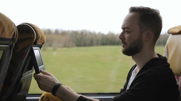 Thumbnail for Young Man Is Riding Bus and Looks at Monitor in Headrest of Seat.