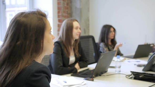 Thumbnail for Three Women Listening and Talking While Sitting at Table with Laptops in Office.