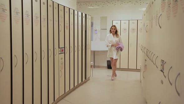 Thumbnail for Woman in Dressing Gown with Towel in Hand Goes To Female Locker Room.