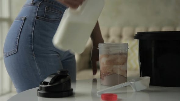 Thumbnail for Young Woman Pours Milk Into Shaker and Shakes It at Home.