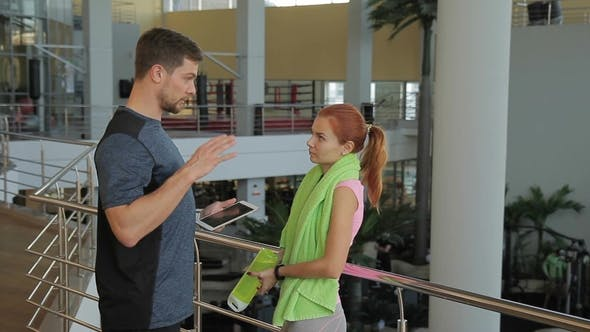 Thumbnail for Young Woman Talking with Trainer Standing in Sports Club.