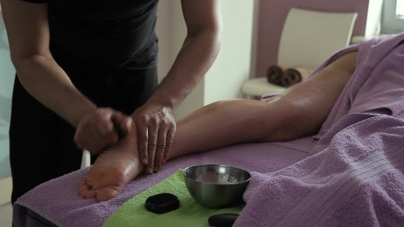 Thumbnail for Masseur Makes a Woman's Foot Massage with Help of Stone