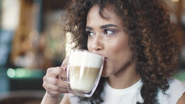 Thumbnail for Beautiful Hispanic Woman Enjoys the Latte in a Cozy Cafe