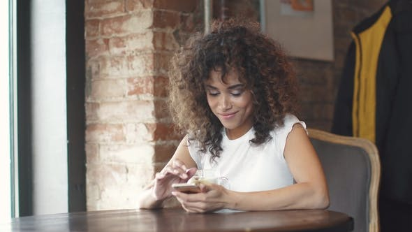 Thumbnail for Attractive Hispanic Girl Using Smartphone and Smiles in a Coffee House.