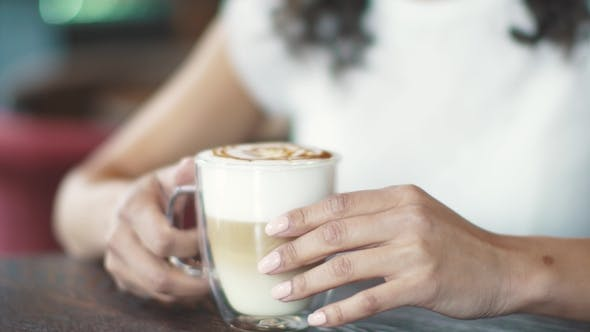 Thumbnail for Beautiful Hispanic Woman Enjoys the Latte in a Cozy Cafe. Female Hands