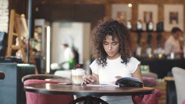 Thumbnail for Young Girl Mulatto Drinks Coffee in a Cafe and Looks at the Menu. Beautiful Hispanic Woman Enjoys