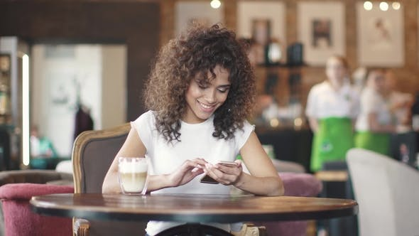 Thumbnail for Portrait of a Mulatto Girl in a Coffee House. Beautiful Hispanic Woman Messaging on Smartphone and