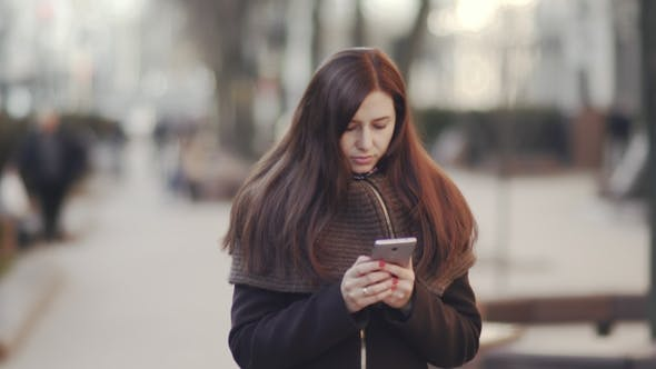 Thumbnail for Young Attractive Woman Is Using a Smartphone in a Big City at Sunset