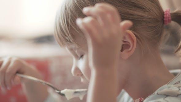 Ein kleines Mädchen isst Brei