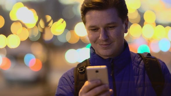 A Young Man Uses a Mobile Phone at Sunset in the City