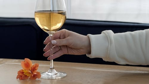 Table in Restaurant with Fresh Flower. Female Hand Takes a Glass of White Wine for Tasting and Puts
