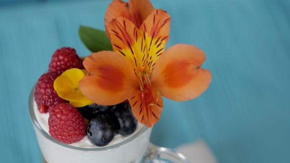 Delicious Fruit Dessert with Blueberries and Raspberries. Woman Decorates Mousse with Beautiful