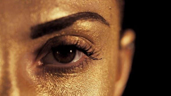 Thumbnail for View of Woman's Face with Beautiful Golden Body Art Looking To Camera, Eye Shines Brightly in the