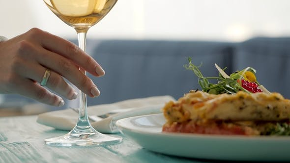 Table in Restaurant. Dish with Seafood Salad, Caviar, Vegetables and greens. Female Hand Takes a