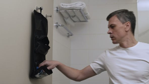 Thumbnail for Man Taking Grooming Accessories From Bag