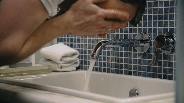 Thumbnail for Crop Man Washing Face in Sink