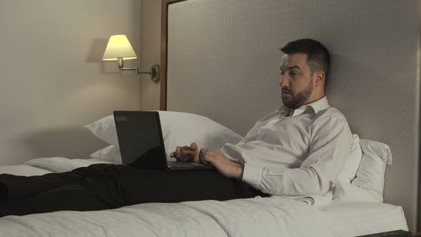 Thumbnail for Businessman Working with Laptop on Bed