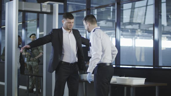 Thumbnail for Security Agent Using a Metal Detector on a Man