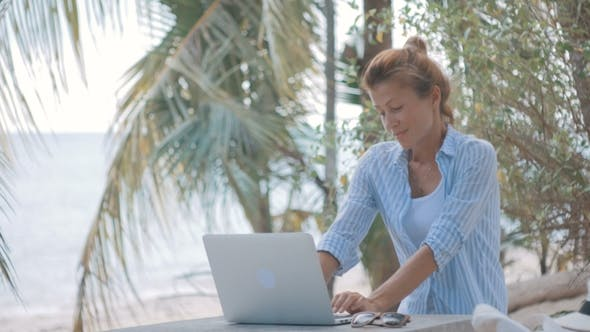 Thumbnail for Young Woman Sitting at the Table with a Laptop with Sea View Behind, Camera Move