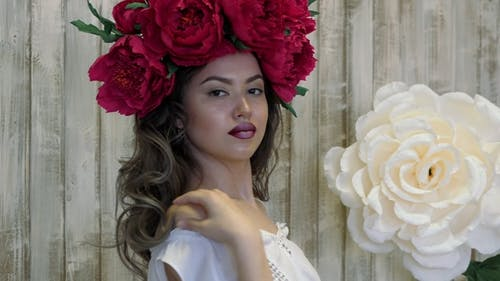 Girl Posing in Front of Camera. Young Woman in a Wreath of Scarlet Peonies on Her Head