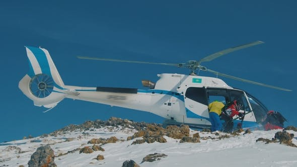 Thumbnail for Heliskiing Skiers Are Disembarked From the Helicopter in the Mountains in Winter.  View