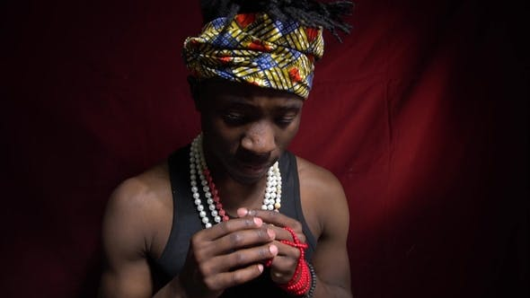 Thumbnail for Ein trauriger Mann aus Angola, sieht erbärmlich an die Kamera, Perlen, Bandana