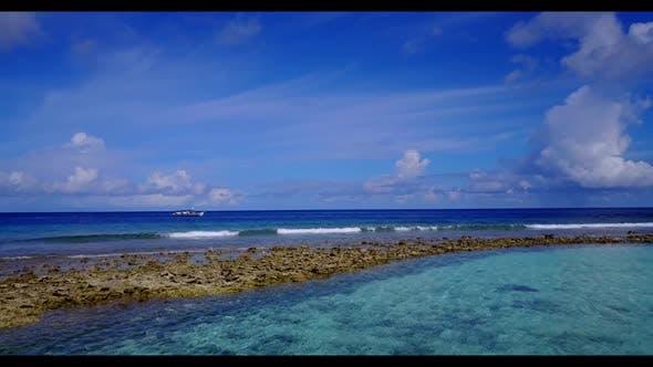 Thumbnail for Luftaufnahme über die Landschaft eines perfekten Küstenstrandurlaubs durch transparente Lagune und hellen Sand