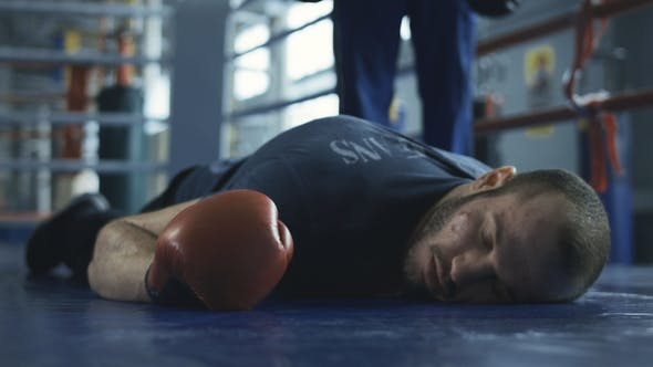 Thumbnail for Unconscious Boxer in Gloves Lying on Ring