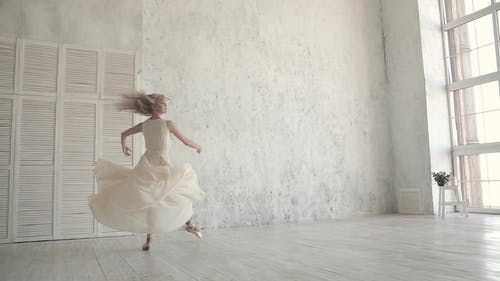 Ballerina in White Light Dress and Pointe Shoes. Conecpt of Lightness and Youth