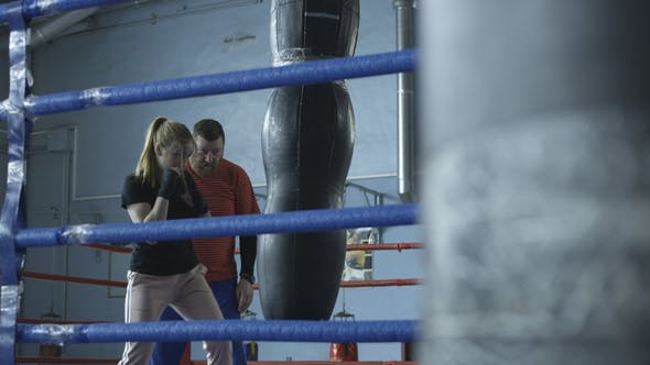 Thumbnail for Girl Boxing Punchbag with Trainer