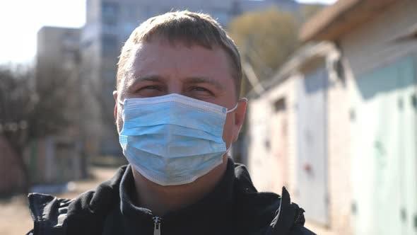 Thumbnail for Porträt des Menschen mit medizinischer Gesichtsmaske steht an der City Street während der COVID-19 Epidemie. Mann tragen