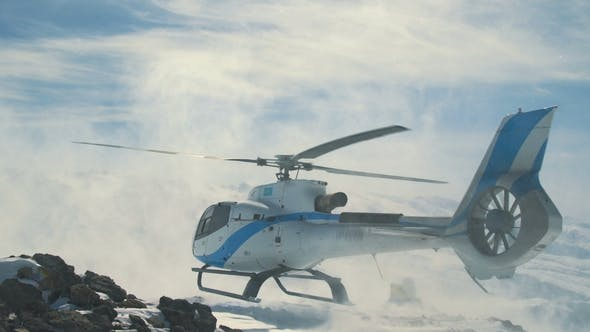 Thumbnail for Heliskiing Helicopter Landed in the Snow Mountains, Raising a Big Cloud of Snow