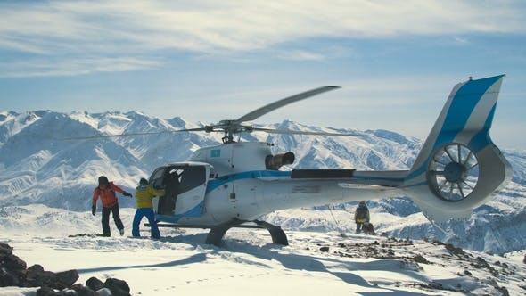 Thumbnail for Skiers Unload Skis From a Landed Helicopter in the Winter Mountains