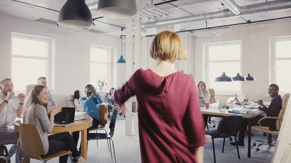 Thumbnail for Camera Follows Caucasian Businesswoman Enter Multi-ethnic Office Doing Funny Dance Walk of Success