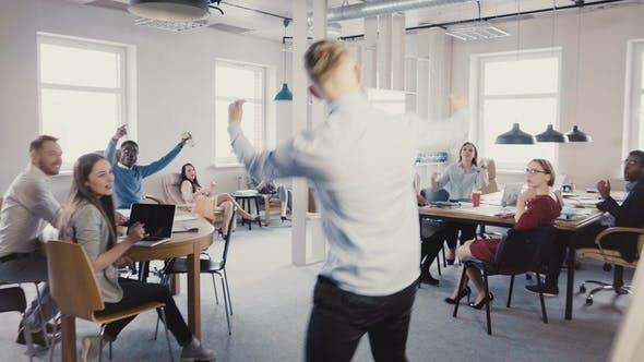 Thumbnail for Camera Follows Happy Businessman Walk Into Office, Doing Funny Celebration Dance. Multi-ethnic