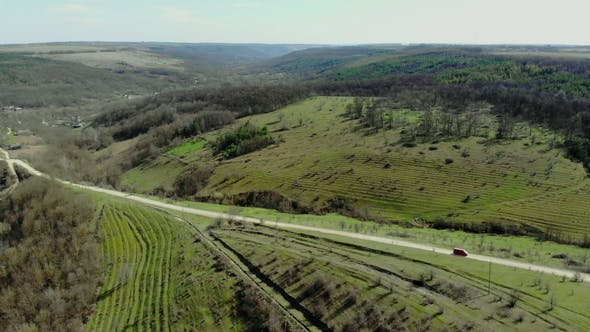 Thumbnail for Drone Flies Over Green Hills and Road with Car Fast Driving. Aerial Top View of Country Road