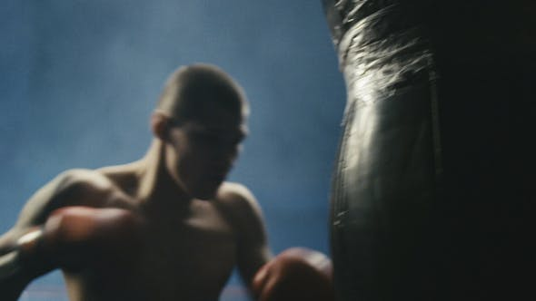 Man Training with Punching Bag in Gym