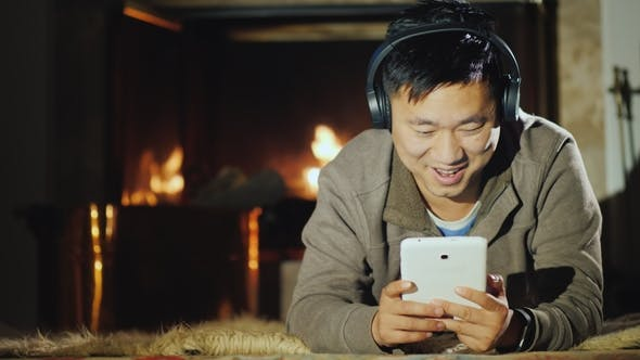 Thumbnail for Happy Asian Man Resting at Home By the Fireplace, Enjoys a Tablet