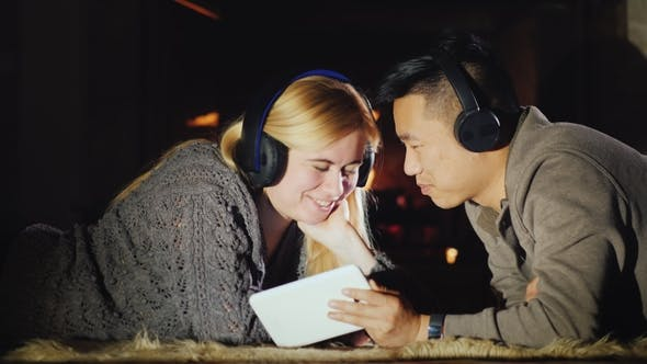 Thumbnail for A Happy Multiethnic Couple Is Resting at Home By the Fireplace, Using a Tablet