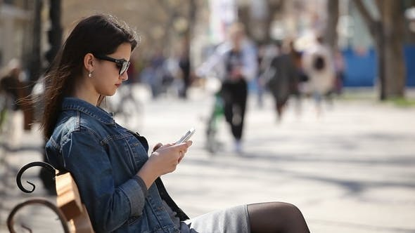 Cover Image for Successful Woman Surfing the Net on Her Smartphone Sitting on an Alley Bench