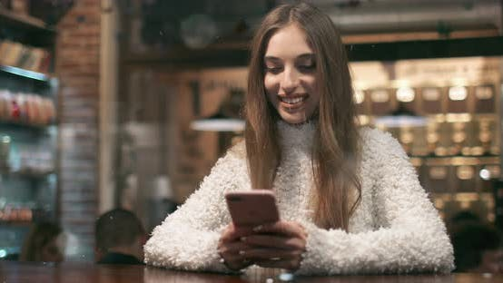 Thumbnail for Smiling Girl Busy Using Smartphone