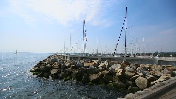 Cover Image for View from pier of small sailing boat floating in open sea, summer rest, sequence