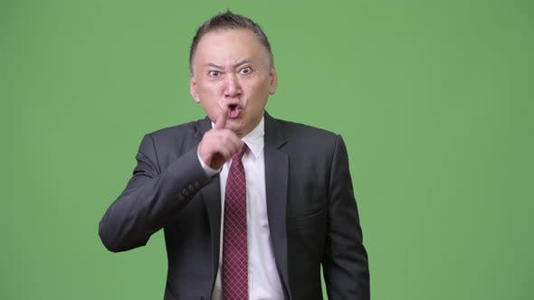 Thumbnail for Mature Angry Japanese Businessman with Finger on Lips