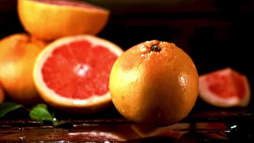 Super Slow Motion Fresh Grapefruit Falls on the Table with Splashes of Water