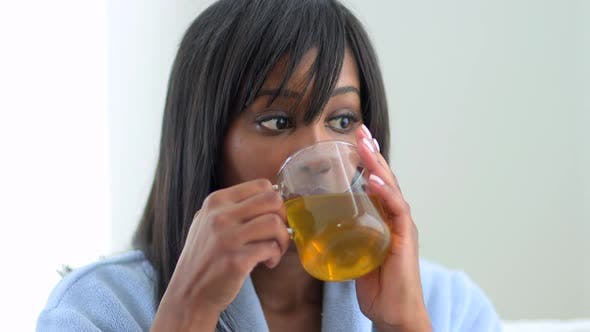 Thumbnail for African American woman drinking tea in robe