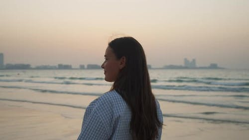 Close Up View of Brunette Woman in Elegant Clothes Walking on Sandy Beach in Dubai