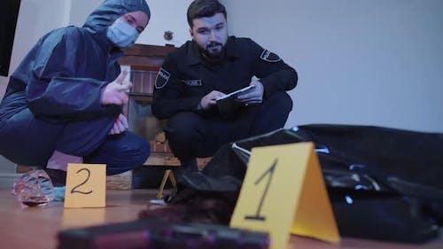 Porträt von ernsthaften kaukasischen Polizisten diskutieren Beweise am Tatort