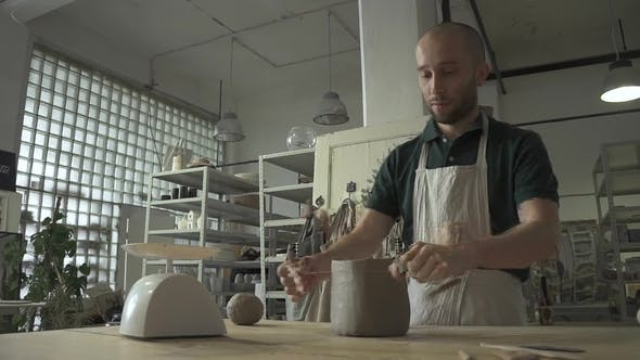 Thumbnail for Male Potter Is Working While Standing at Table in Pottery Workshop