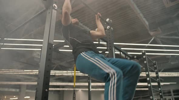 Young Caucasian Athlete Doing a Flip Lift in a Gym with Haze and Modern Lighting