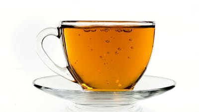 Tea Pouring. Tea Being Poured Into Glass Transparent Tea Cup. Tea Time. Transparent Glass Teapot and